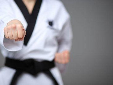 The hand of karate girl in white kimono and black belt training karate over gray background.